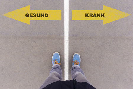 footsie: Gesund  Krank (German for healthy or sick) direction sign text on asphalt ground, feet and shoes on floor, personal perspective footsie concept Stock Photo