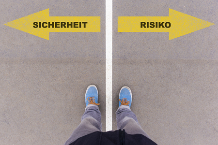 sicherheit: Sicherheit  Risiko(German for safety and risk) direction sign text on asphalt ground, feet and shoes on floor, personal perspective footsie concept