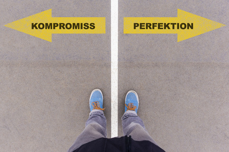 footsie: Kompromiss  Perfektion (German for compromise or perfection) direction sign text on asphalt ground, feet and shoes on floor, personal perspective footsie concept