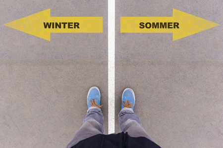Winter  Sommer (German for winter and summer) direction sign text on asphalt ground, feet and shoes on floor, personal perspective footsie concept