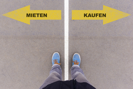 footsie: Mieten  Kaufen (German for rent or buy) direction sign text on asphalt ground, feet and shoes on floor, personal perspective footsie concept