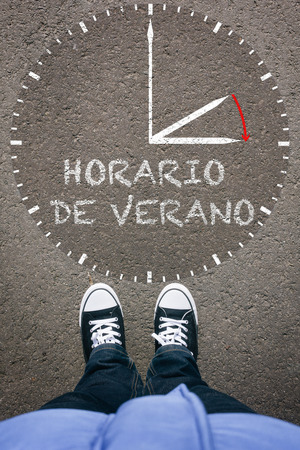 footsie: Horario de Verano, Spanish Daylight Saving Time clock with pair of legs and shoes on asphalt ground, high angle footsie or flortrait, personal pespective from above.