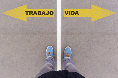 footsie: Trabajo y Vida, Spanish text for Work and Life, direction sign text on asphalt ground, feet and shoes on floor, personal perspective footsie concept Stock Photo