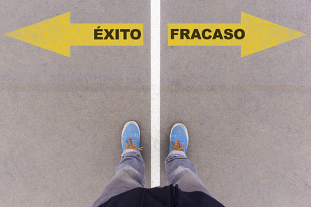 footsie: Exito y Fracaso, Spanish text for Success and Failure, direction sign text on asphalt ground, feet and shoes on floor, personal perspective footsie concept