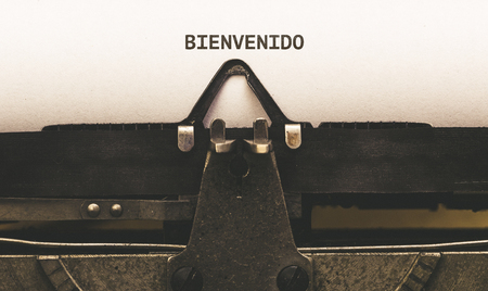 bienvenido: Bienvenido, Spanish text for Welcome, on paper in vintage type writer machine from 1920s Stock Photo