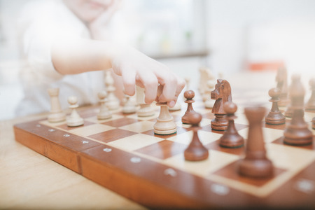 Young boy moving a chess figure on a board, wide angle view with lens flare processing