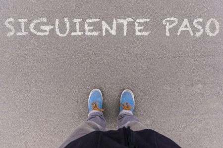 footsie: Siguiente paso, Spanish text for Next Step, text on asphalt ground, feet and shoes on floor, personal perspective footsie concept