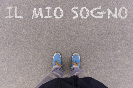 Il mio sogno, Italian text for My Dream, text on asphalt ground, feet and shoes on floor, personal perspective footsie concept Zdjęcie Seryjne