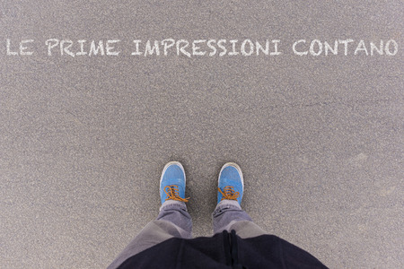footsie: Le prime impressioni contano, Italian text for First Impressions Count, text on asphalt ground, feet and shoes on floor, personal perspective footsie concept