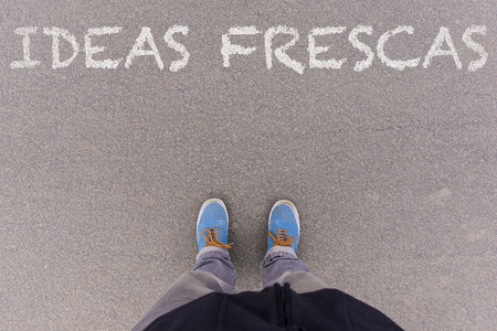 footsie: Ideas frescas, Spanish text for Fresh Ideas, text on asphalt ground, feet and shoes on floor, personal perspective footsie concept