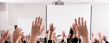 Raised hands and arms of large group of people in class room, audience voting in professional education surrounding, selective focus with anonymous people. Stock Photo