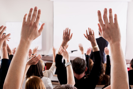 Raised hands and arms of large group of people in class room, audience voting in professional education surrounding, selective focus with anonymous people. Stockfoto