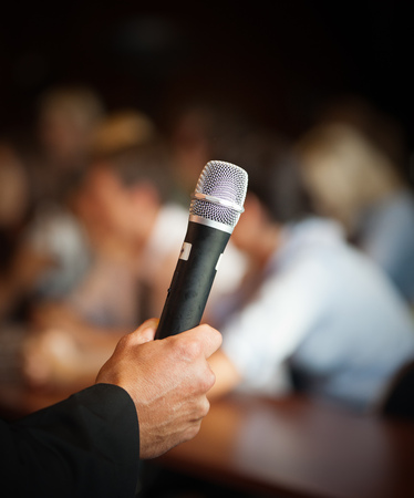 large group of business people: Hand holding microphone in front of large group of people in class room, audience in professional education surrounding, selective focus with anonymous people.