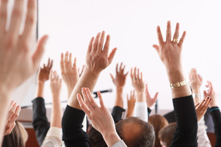 referendum: Raised hands and arms of large group of people in class room, audience voting in professional education surrounding, selective focus with anonymous people. Stock Photo