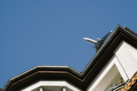 Airplane flying low over buildings in Berlin Pankow during approach to airport Tegel