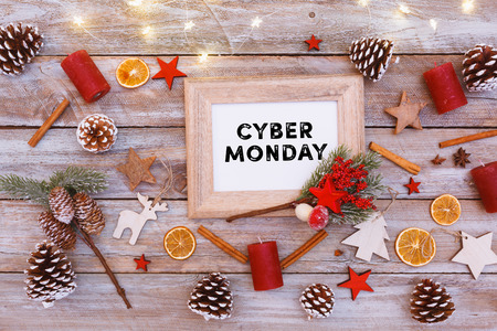 Cyber Monday text in frame on christmas flat lay table with image photo frame and light chain shining, including copy space