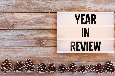 Year in Review text in lightbox on winter decorated table with pine cones Stock Photo