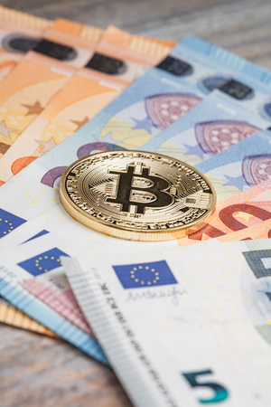 hype: Symbolic golden bit coin lying on top of Euro banknotes on a table