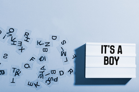 Light box with boy baby text announcement on manly blue background, surrounded by letters in chaotic order Stock Photo