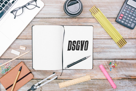 DSGVO (German for new regulation effective May 2018 in European Union on general data protectionprivacy) message in writers journal or diary with blank space on paper, pencil for writing, grunge office deskt flat lay shot from above