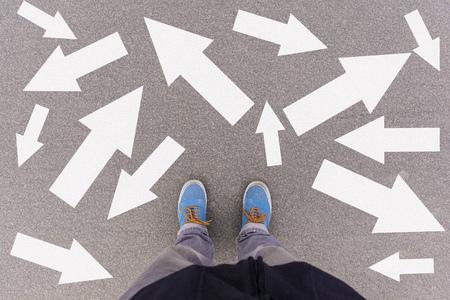 Flechas de dirección confusas en el suelo asfaltado, pies y zapatos en el piso, concepto de orientación personal