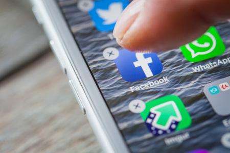 BERLIN, ALLEMAGNE - 6 JUIN 2018 : Fermez le doigt en supprimant l'application Facebook sur l'écran d'un iPhone 7 Plus avec un arrière-plan personnalisé. Éditoriale