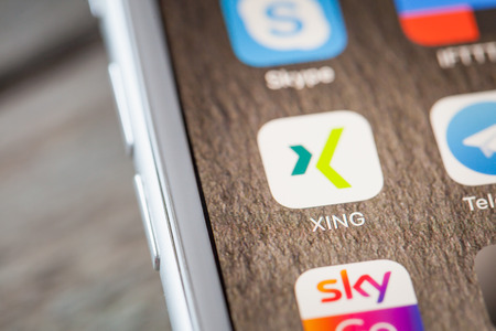 BERLIN, GERMANY - JUNE 6, 2018: Close up to Xing professional network app on the screen of an iPhone 7 Plus with personalized background. Editorial