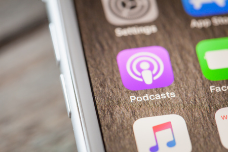 BERLIN, GERMANY - JUNE 6, 2018: Close up to Apple Podcasts app on the screen of an iPhone 7 Plus with personalized background. Editorial