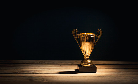 Golden sports trophy cup on wood desk with dramatic strong contrast light and shadow