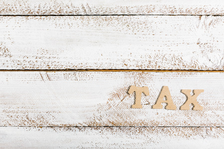 Tax word as headline on white painted table Фото со стока
