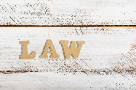 Law word as headline on white painted table Фото со стока
