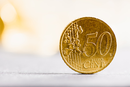 Close-up macro to 50 Euro cents coin with shallow depth of field and overexposed bright background 스톡 콘텐츠