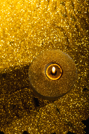 Close-up macro with shallow depth of field of flame in christmas candle with gold glitter background Reklamní fotografie