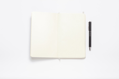 White notebook lying on white table in minimum setup as organized writing and author concept