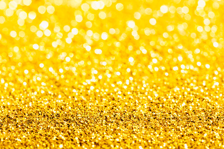 Gold glitter macro close-up texture with shallow depth of field and bokeh background, luxury value concept for christmas or birthday greetings and presents Stock Photo