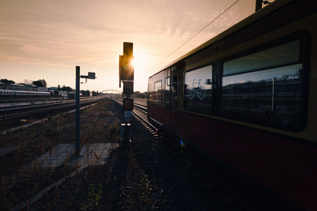 Regional train (S-Bahn) driving with green light at early morning sunrise light on tracks in Berlin, Germany. Stock fotó