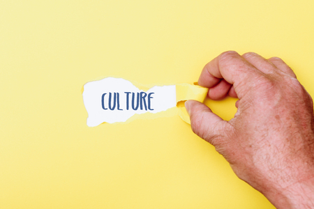 Culture written word, hand ripping shreds of paper from foreground to reveal secret in background