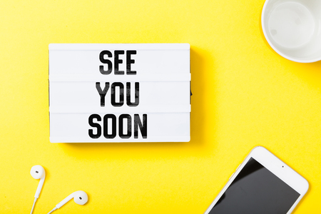 See You Soon message written in light box on yellow technology desk flat lay