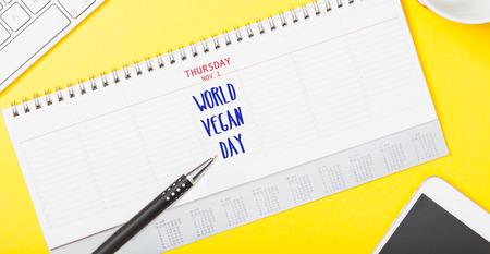 World Vegan Day message written in calendar on yellow technology desk flat lay Standard-Bild