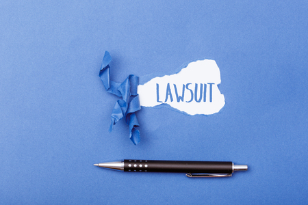 Lawsuit word message written on ripped pieces of cardboard paper