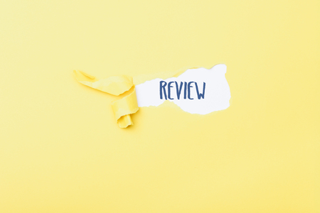 Review word message written on ripped pieces of cardboard paper