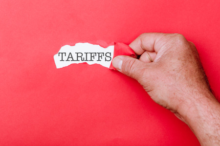 Tariffs word message written on ripped pieces of cardboard paper