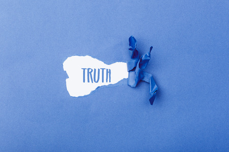 Truth word message written on ripped pieces of cardboard paper