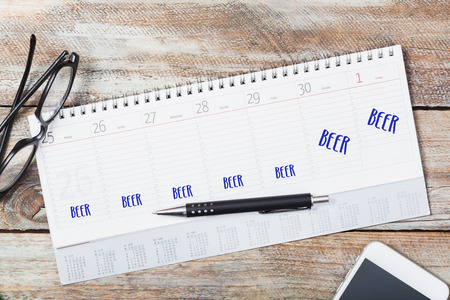 Beer message written in every day of calendar on wood desk technology desk flat lay