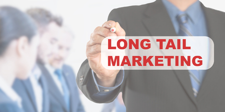 Long Tail Marketing text, male hand in business wear holding a thick pen writing, with office team blurred in background, digital composing.