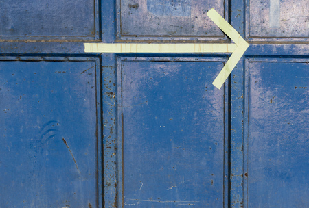 Yellow arrow on blue steel container, pointing to the right direction Stock fotó