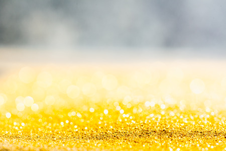 Gold glitter macro close-up texture with shallow depth of field and bokeh background, luxury value concept for christmas or birthday greetings and presents 写真素材