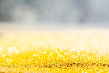 Texture de gros plan macro de paillettes d'or avec une faible profondeur de champ et fond de bokeh, concept de valeur de luxe pour les voeux et cadeaux de Noël ou d'anniversaire
