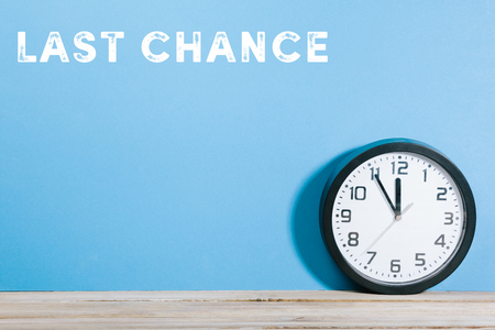 Last Chance text on blue colored background wall with black clock on wooden desk