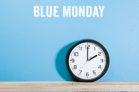 Blue Monday text on blue  colored background wall with black clock on wooden desk Foto de archivo